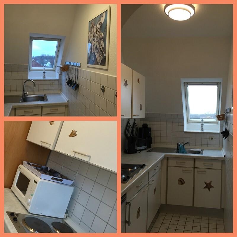 Kochbereich mit Herdplatten, einer Mikrowelle, einem Dachfenster über der Spüle, Werkzeuge und ein Bild mit Besteck an der Wand