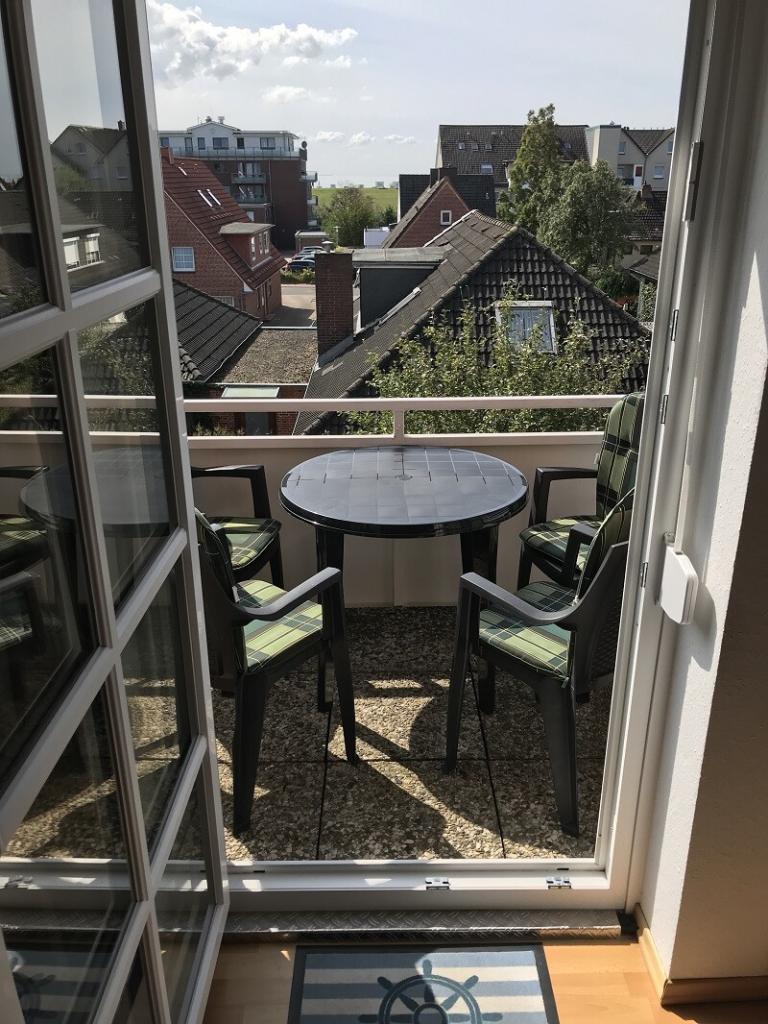 Blick vom Wohnzimmer auf den Balkon mit Tisch und 4 Stühlen mit Sitzpolster